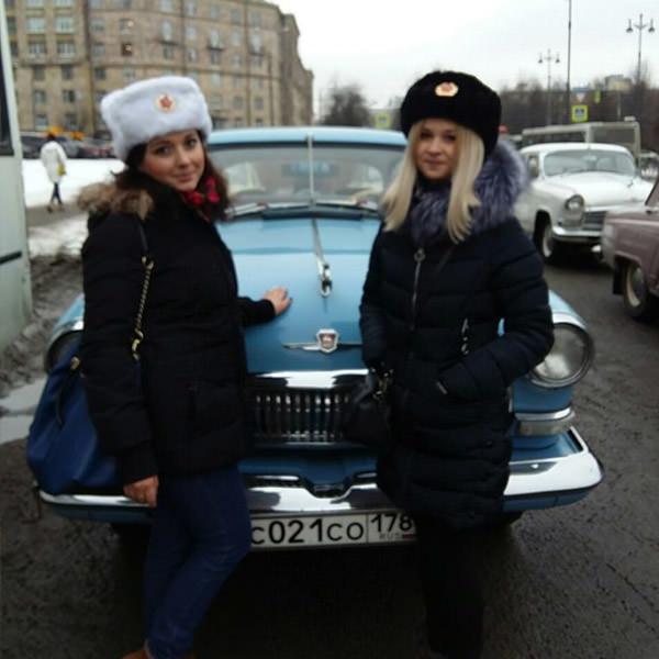 Aida sous la forme d'un agent du KGB lors d'une quête avec des touristes français sur le fond d'une voiture rétro. Atmosphère de Léningrad